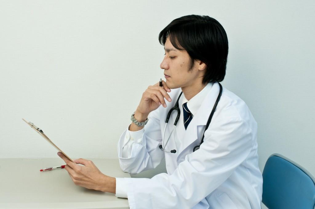 カルテをじっくりと分析する若き医師