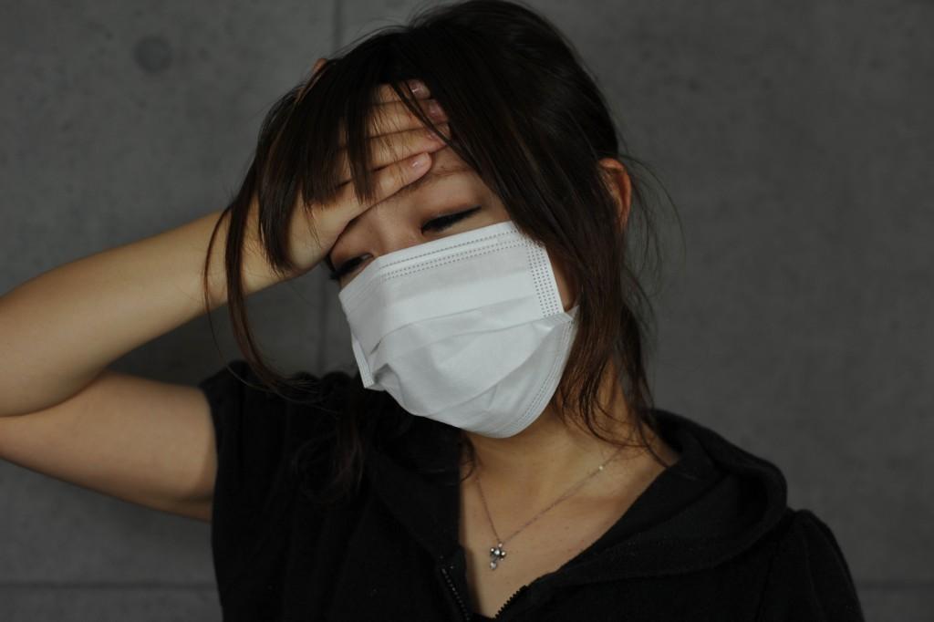 発熱で体調が悪化しマスクを装着する女性
