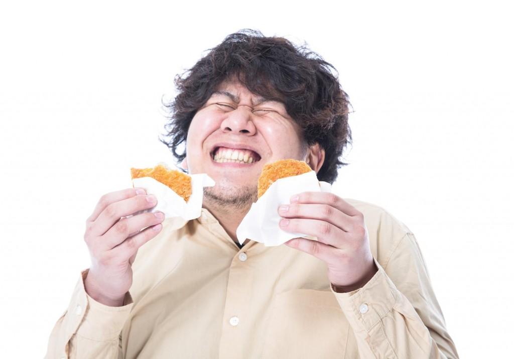両手にメンチカツを持って満面の笑みを浮かべる肥満男性