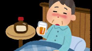 ベッドの中でウイスキーを飲む男性(寝酒)